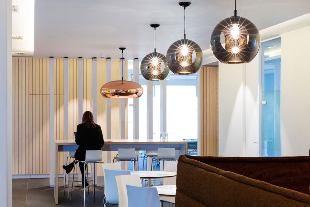 Employee breakout space with white tables and high top counter with modern lamps hung overhead.