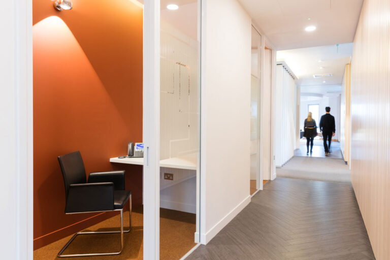 Phone room with orange wall, outside a corridor laid with gray wood-look flooring in a herringbone pattern.