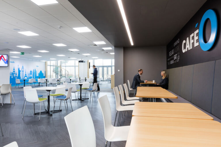 Employee cafe area with white chairs, and pale wood tables, a blue and white graphic of important buildings from around the world adds interest.
