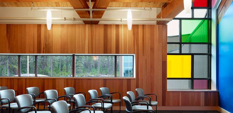 Cedar lines the walls of a meeting or conference room with a geometric window with coloured translucent panels.
