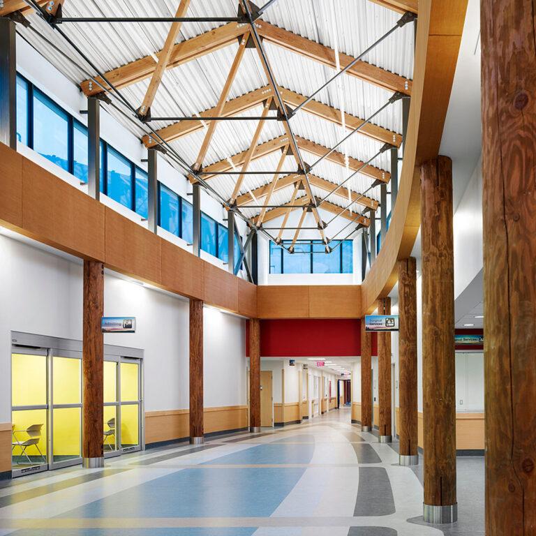 Rectangular ambulatory lobby with clerestory window, supported by raw cedar poles.
