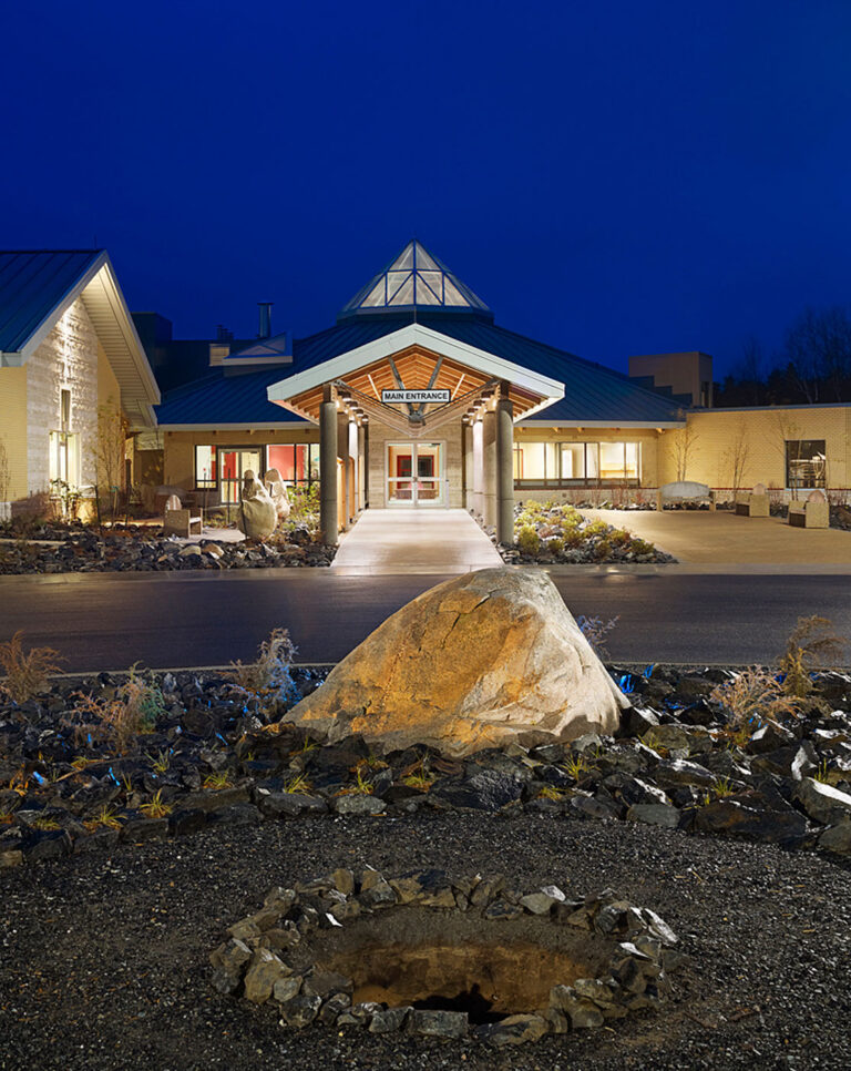 Exterior view of health centre shows main entrance with point of octagonal skylight illuminated at night.