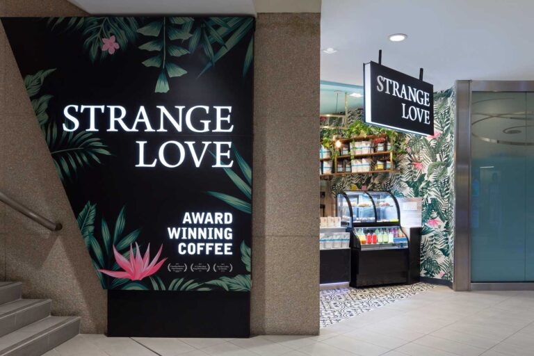 Feature brand wall at Strange Love Coffee with tropical leaf decoration.