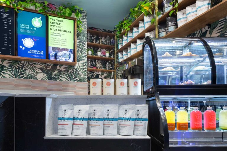 Counter at Strange Love Coffee showing latest roasts in an inset cutout next to a fridge with prepared foods.