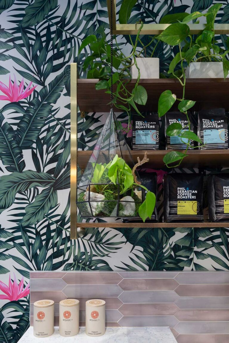 Detail of tropical wallpaper and display shelving with roasted coffee at Strange Love Coffee