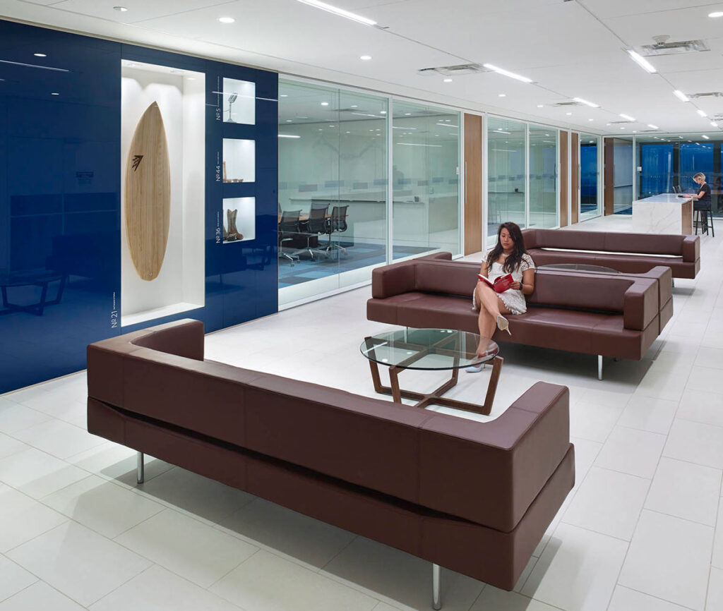 A woman sits on a dark leather couch in the Visa office, a feature of company memoribilia is inset into the wall nearby.