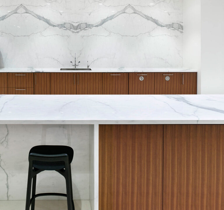 Company cafe with white marble counters and wood cabinetry.