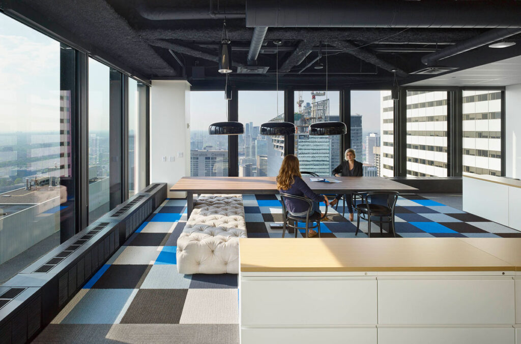 Casual meeting breakout space with table and tufted seating below.
