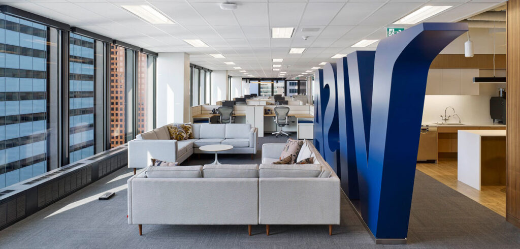 A giant 3D feature element with the company name stands next to a seating area with sofas and employee workspaces beyond.