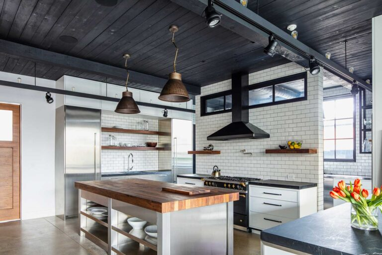 Chefs kitchen with large butcher block island and walls lined in white subway tile.