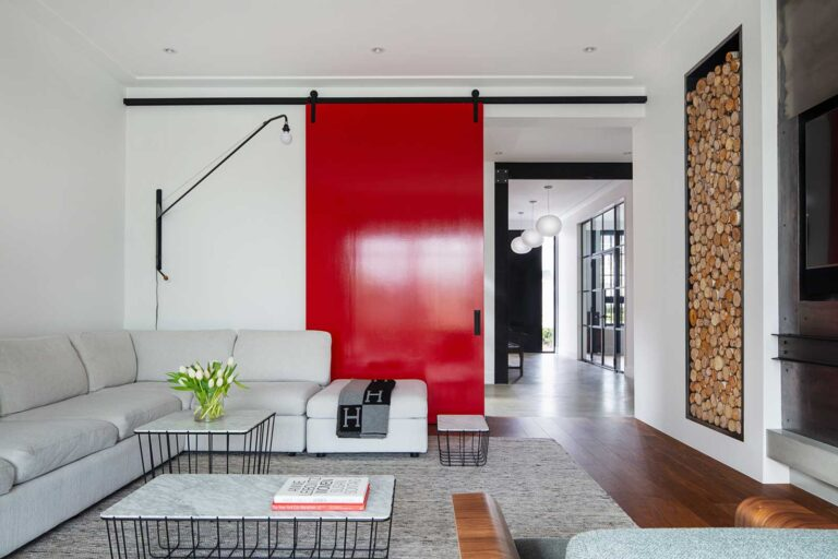 Family room with wood floors, large white sectional and eye-catching red sliding door.