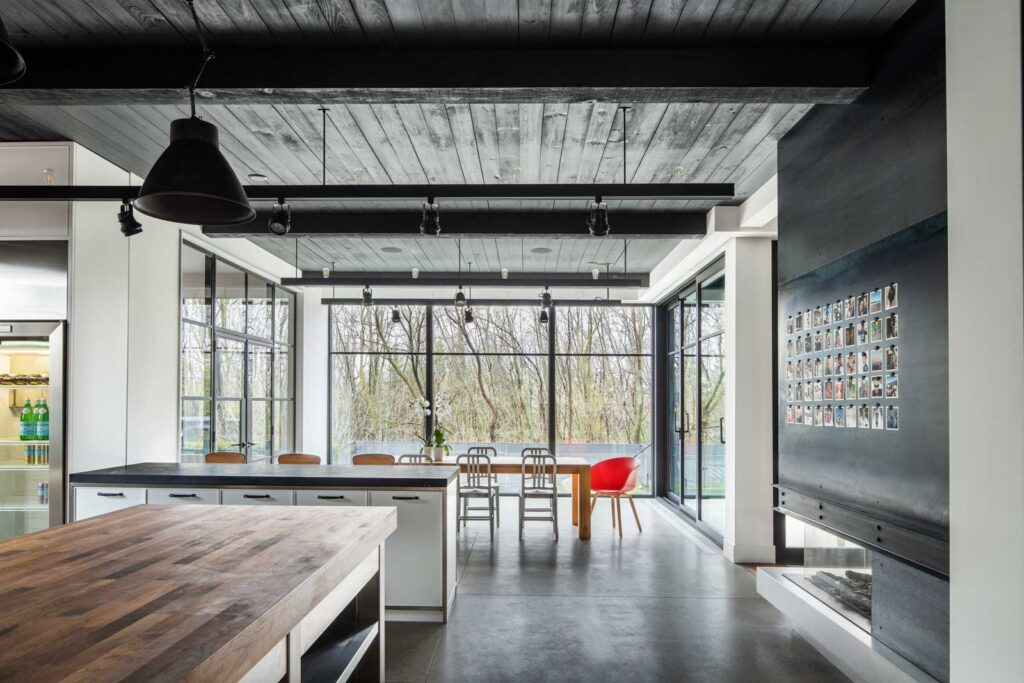 Kitchen and dining room with dark, poured concrete floors and a wood ceiling.