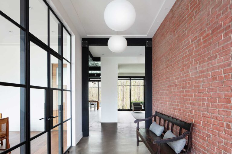 Entryway with poured concrete floors, brick wall on right and glass panelled wall on left.