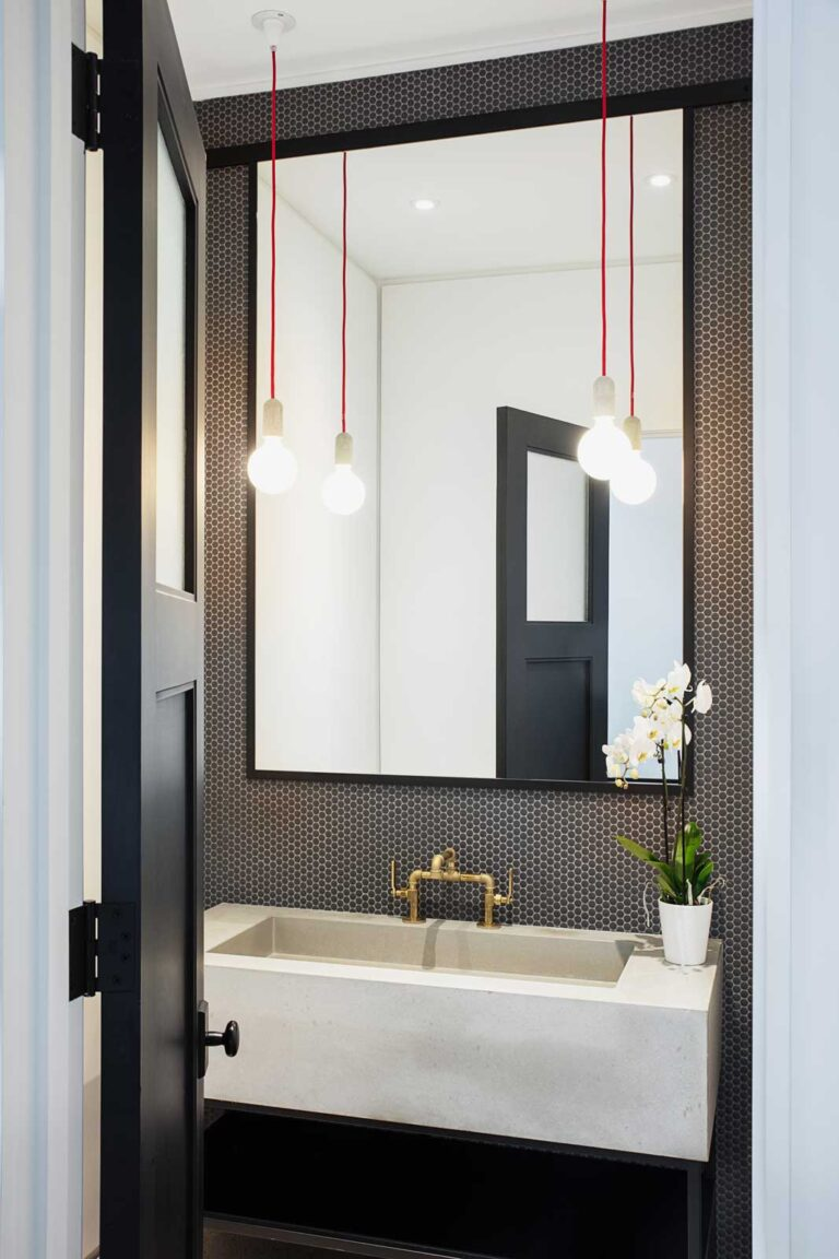 Powder room with black tiling up walls and large white sink with brass tap.