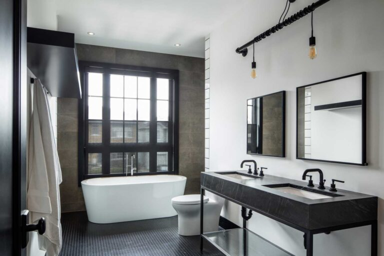Master bathroom with freestanding tub, white walls and white undermount double sinks in black stone.