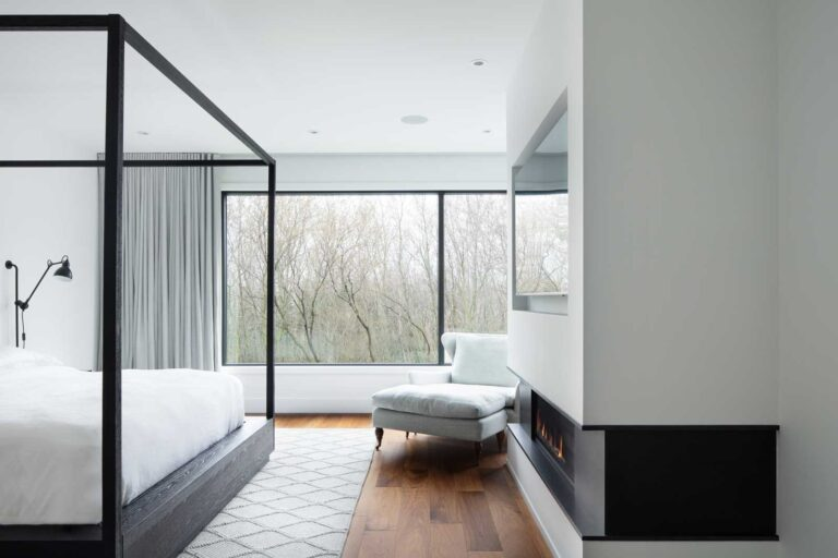 Master bedroom with wood floors, large plank flooring, white walls and an inset fireplace.