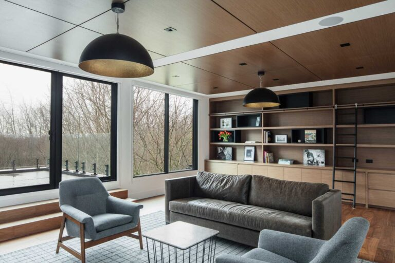 Family room with built in bookshelves, wood lined ceiling and gray and leather seating area.