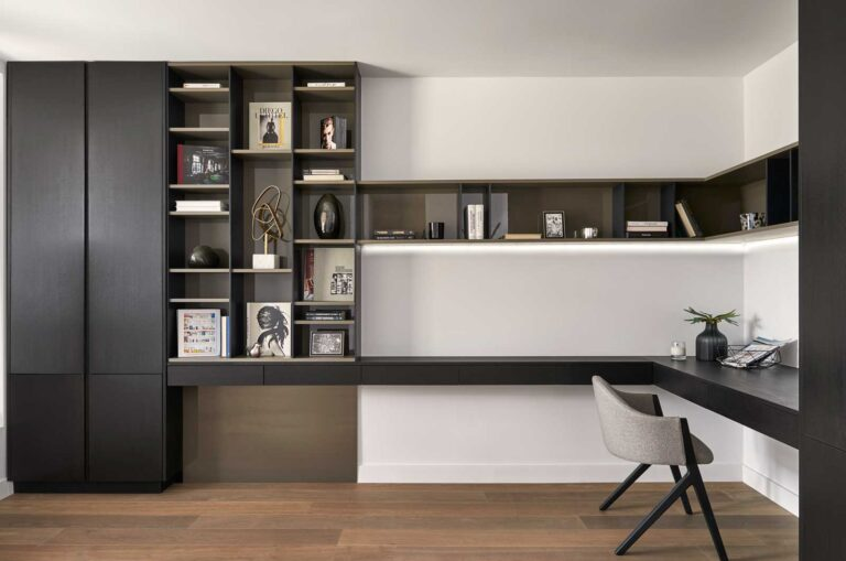 A set of black shelves with nooks abutts a long floatingdesk with a shelf above.