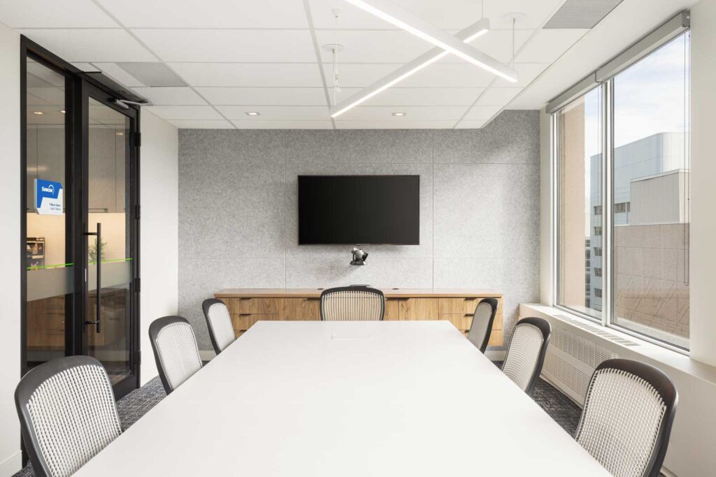 Meeting room with window viewas and a gray felt wall hung with a TV.