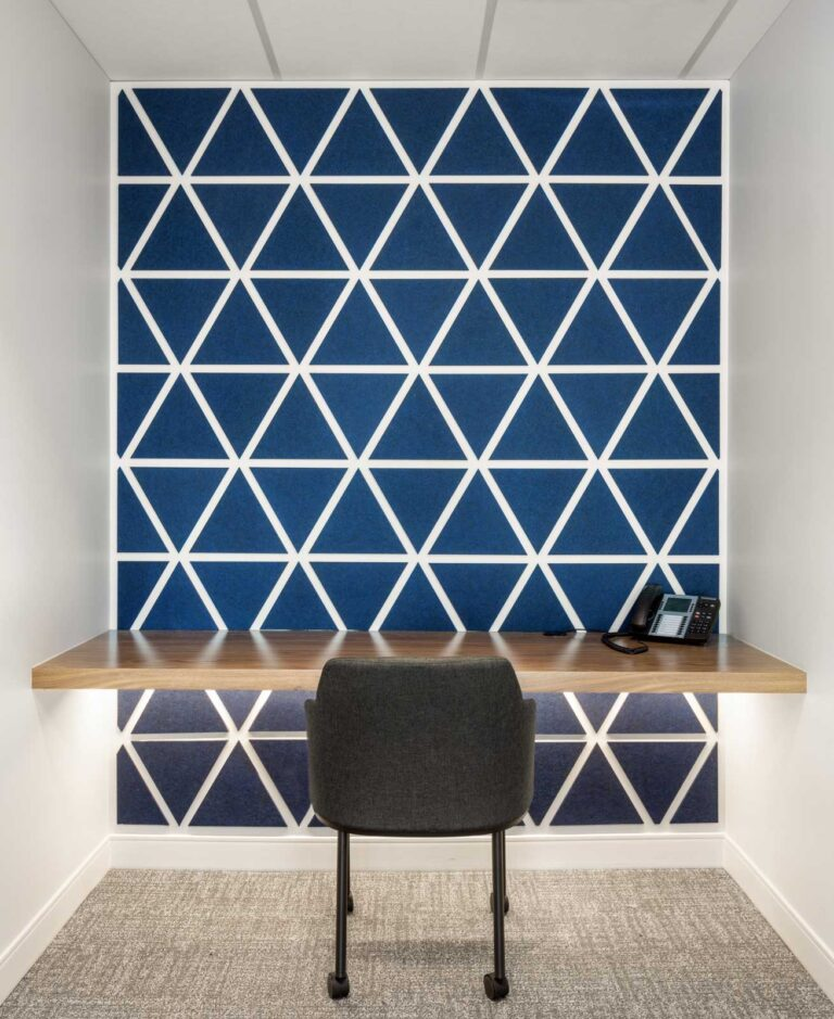 Private phone room with blue and white geometric wall and wood slab hung table.