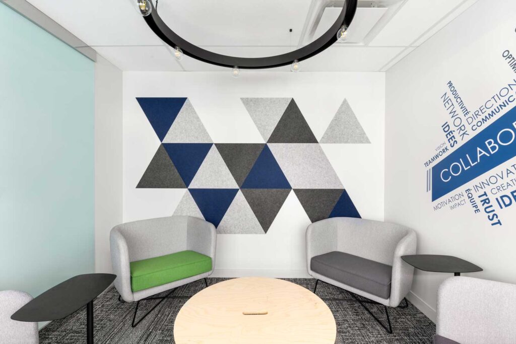 Lounge with triangular acoustical panels in gray and blue with a word could of motivational words.