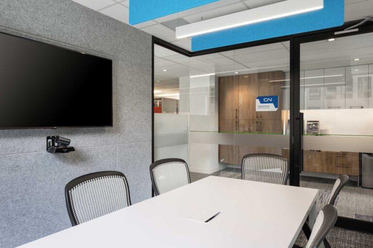 Small meeting room with glass walls and blue and white acoustical partitions above.