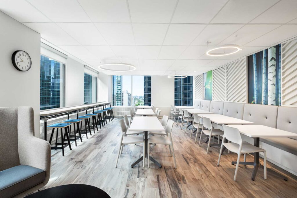 Employee cafeteria with booth seating along the right wall tables and chairs in the middle and stools against the window.