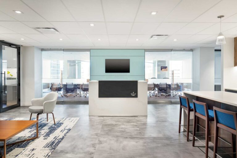 Reception area to large glass walled board room with gray flooring and a lounge with patterned blue and white carpet.