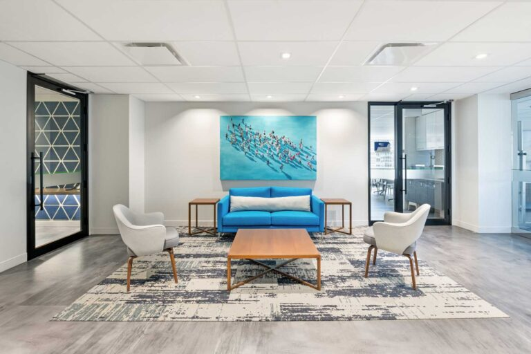 Lounge area with blue and white patterned carpet, blue white and wood seating and a piece of art with people walking on a blue background.