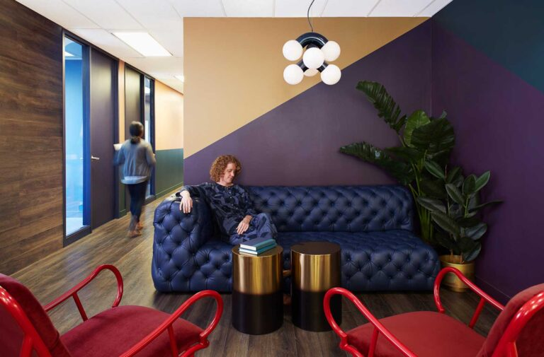 A tufted blue leather couch against a wall with graphi accents is the welcome to this office space.
