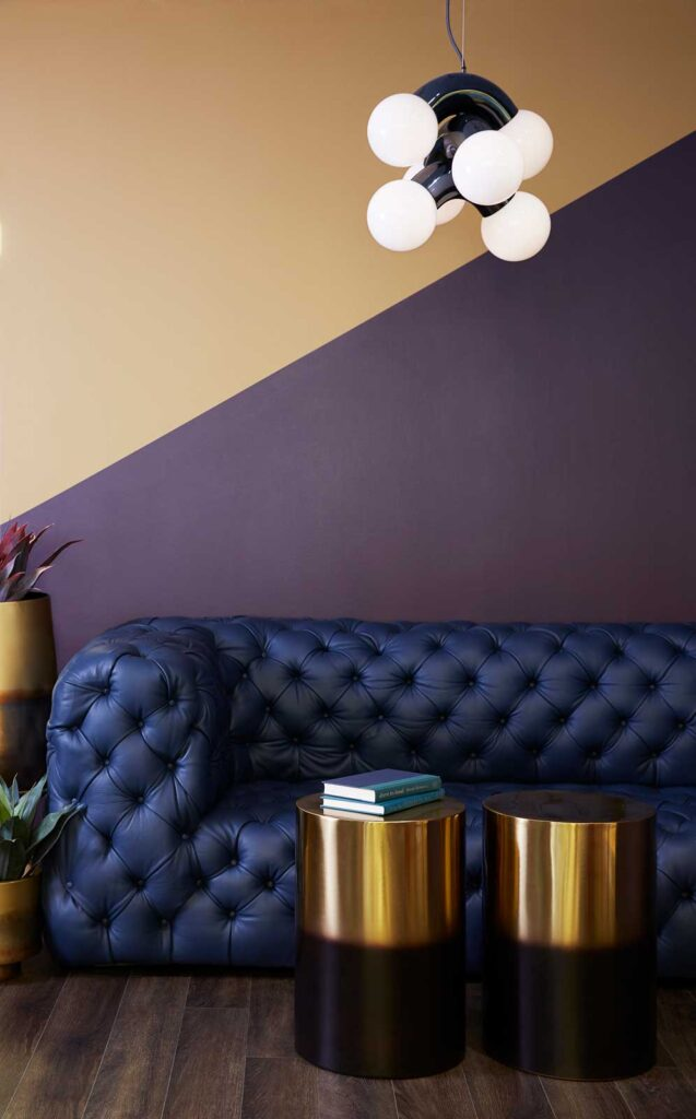 Two brass topped occasional tables in front of a blue tufted leather couch with a modern pendant lamp overhead.