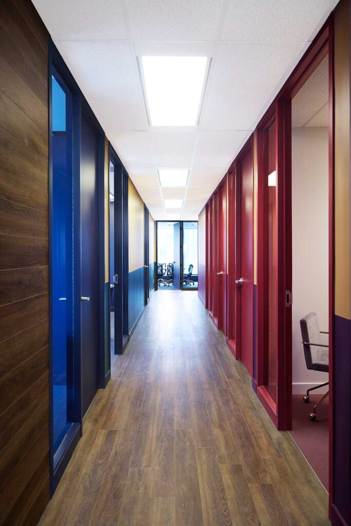 A view of a hallway with blue trimmed doors on the left and red trimmed doors on the right.