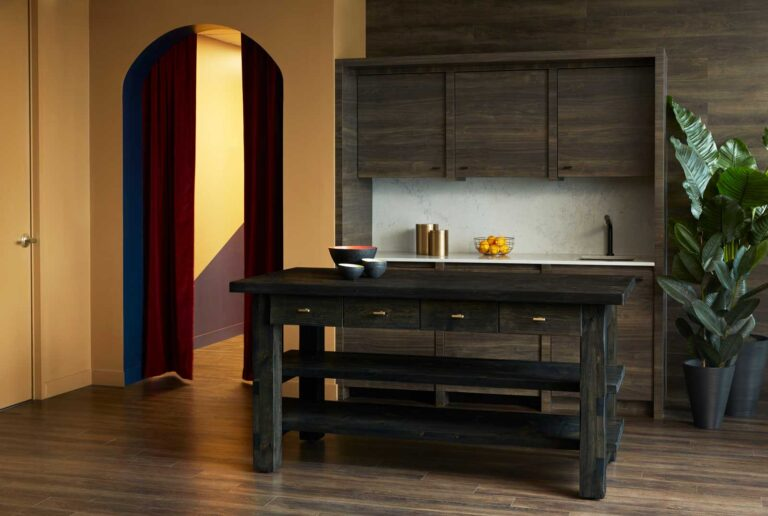 Office kitchen area with wood lined walls and island, with gold painted walls and an archway hung with a red curtain.