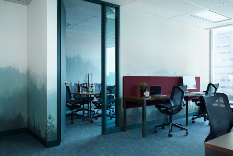 Hot desk area with adjacent meeting room painted with a forest landscape.