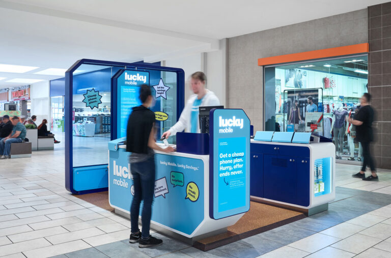 A customer and staffperson interact at a Lucky mobile kiosk in a mall.