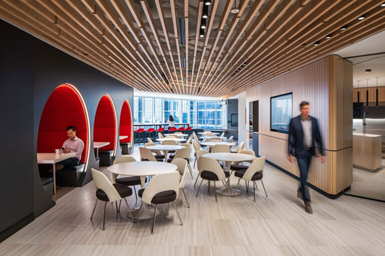 Cafeteria and lunchroom space with corved booth spaces and bright four top tables and chairs.