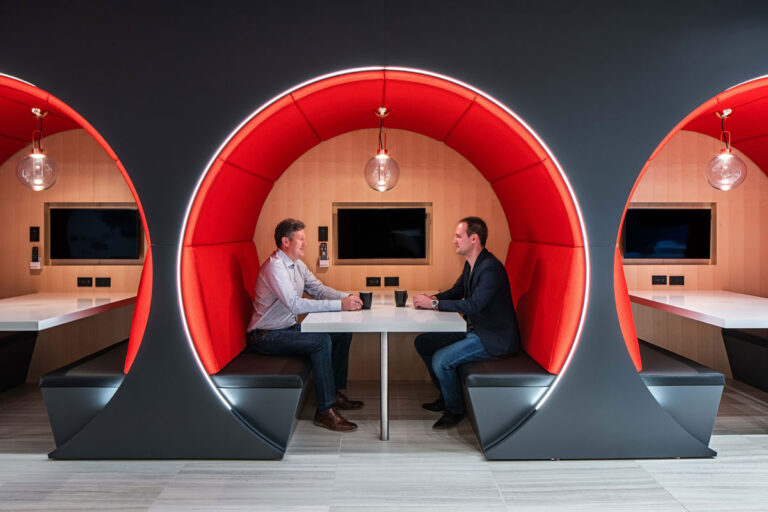 Two men set in a round booth tunnelled into a matte black wall, lined with plush red seating.