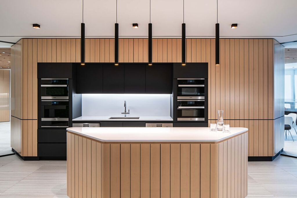 Blond wood panelling lines this sleek employee kitchen area.