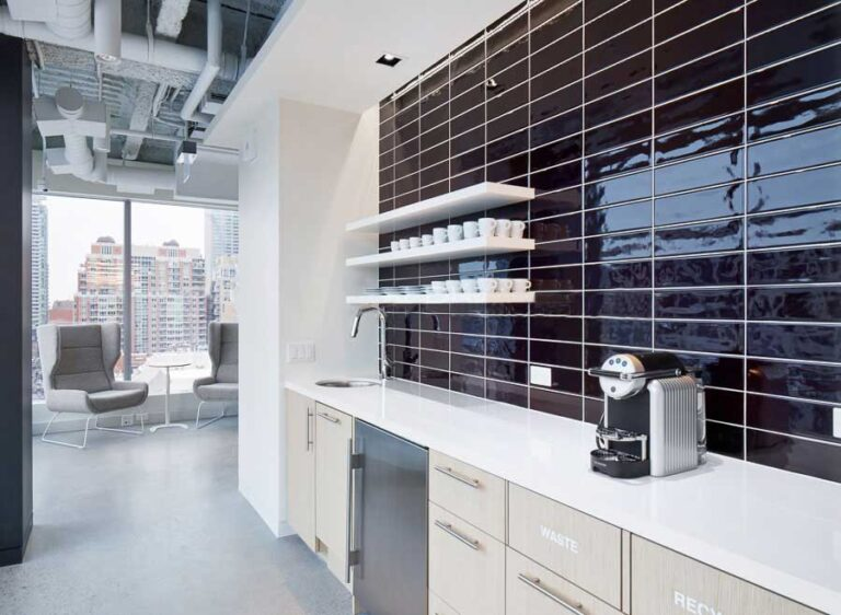 Coffee and hot drink station with black tiled wall, open shelving for cups and pale cabinetry below the counter.