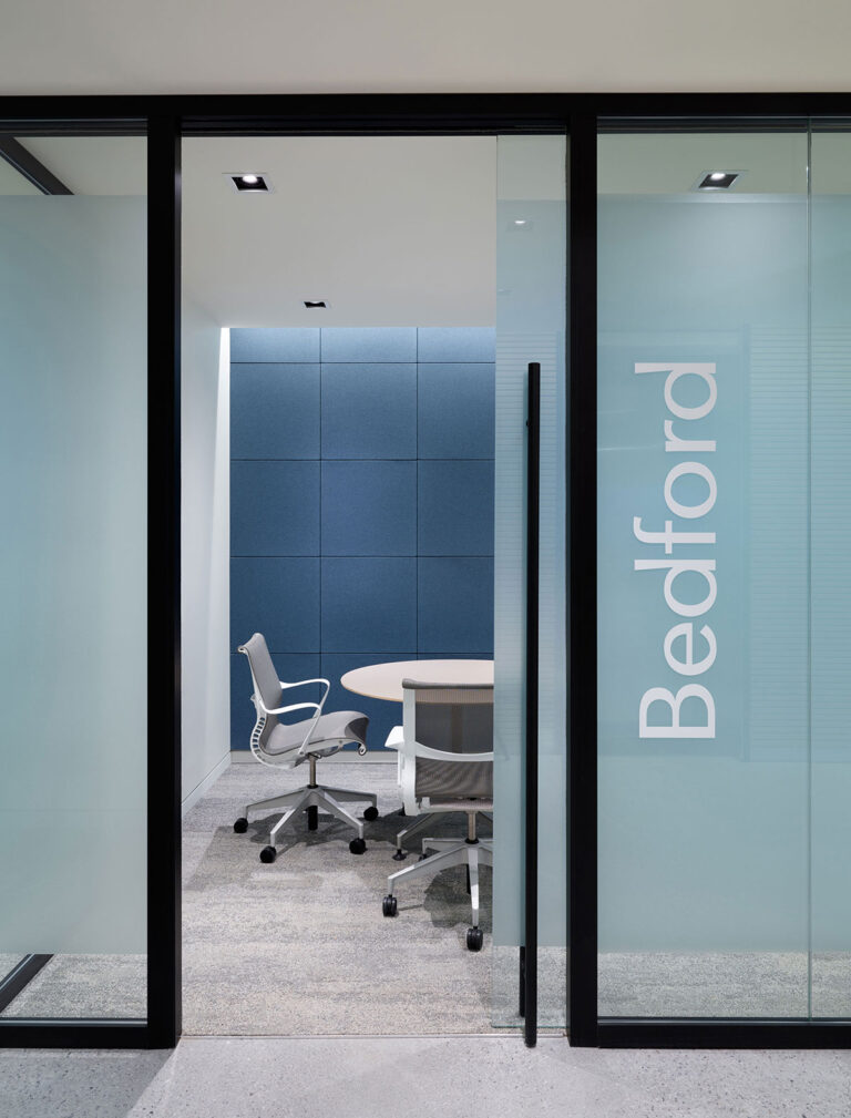 Enclosed interview rooms are defined with frosted glass moveable walls and blue acoustical panels.