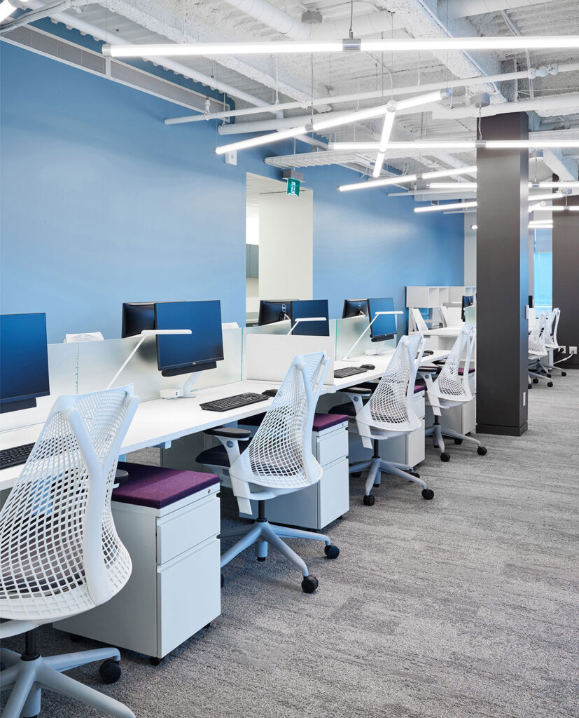 Employee workstations in white with matching seating against a calm blue wall. Modern fluorescent lighting crisscrosses overhead.