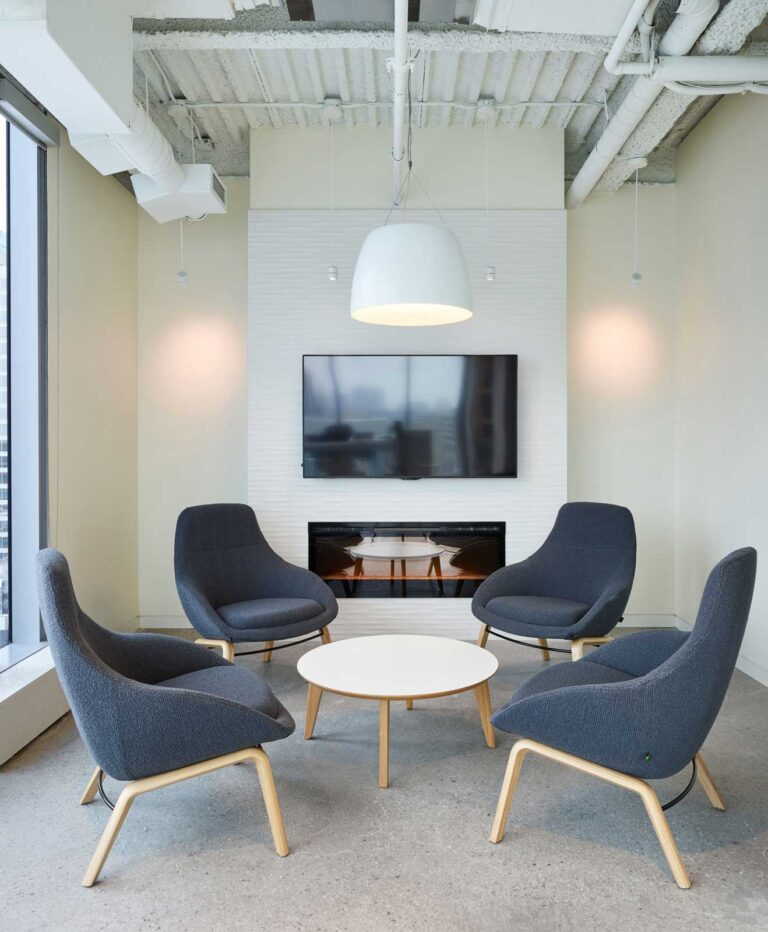 Employee lounge with white walls, dark gray lounge chairs around a low round table.