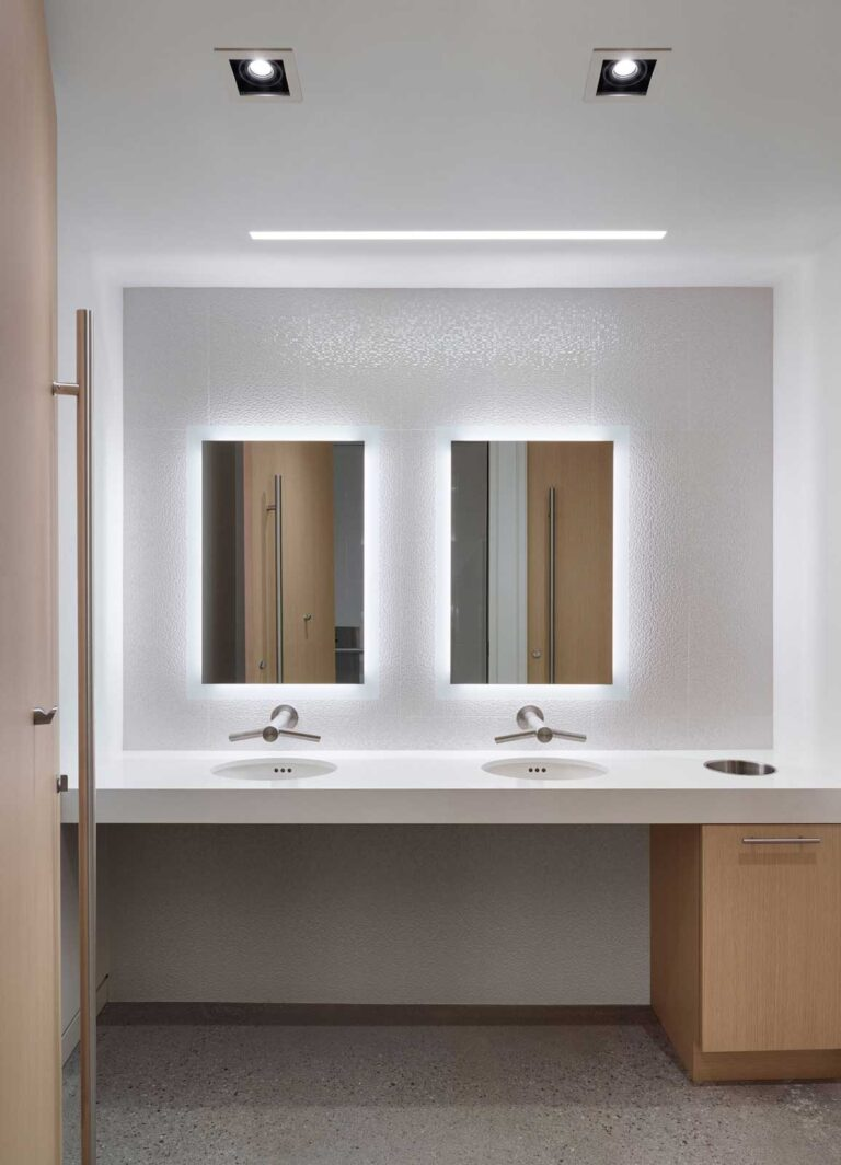 Fresh white bathroom area with two automatic sinks and mirrors with illumination behind.