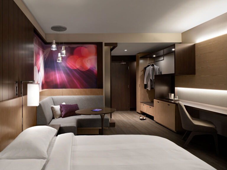 Hotel room with brown and purple colour scheme, and many horizontal surfaces to leave luggage and bags.