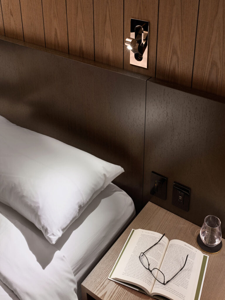 Detail view of bed with dark brown headboard and a sleek brass reading light above.