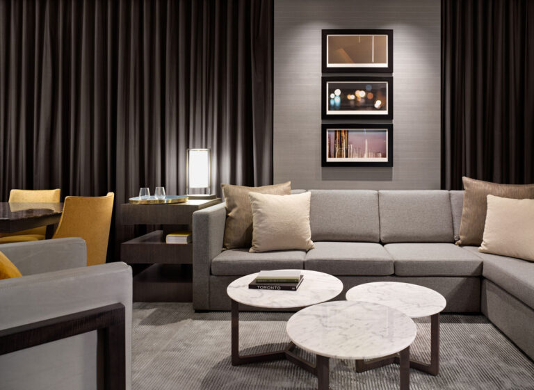 Seating area in a hotel room with long gray couch, low round tables and a gray and yellow colour scheme.