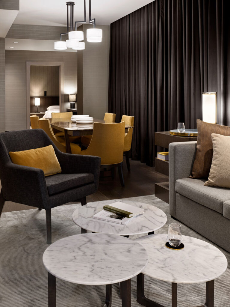 Hotel suite with rich, dark curtains, long dining table with yellow chairs and a seating area with gray couch and yellow cushions.