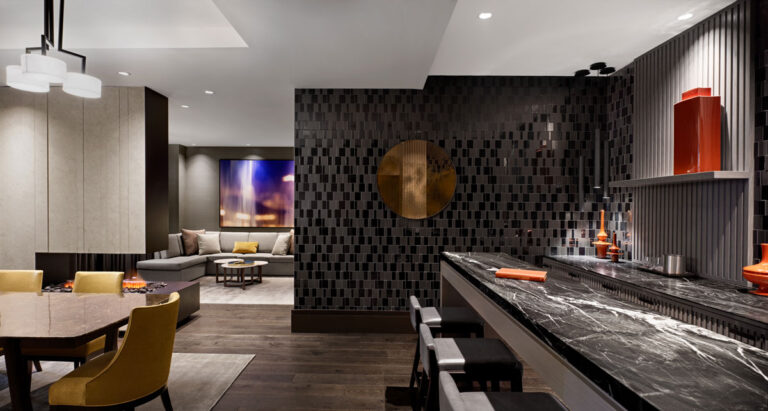 Large guest suite in hotel room with black textured wall, dining table with yellow chairs and special fireplace detail.