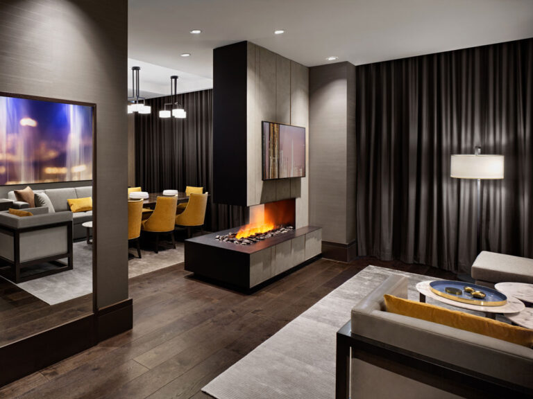 Lounge in hotel suite with special fireplace detail and dining area.