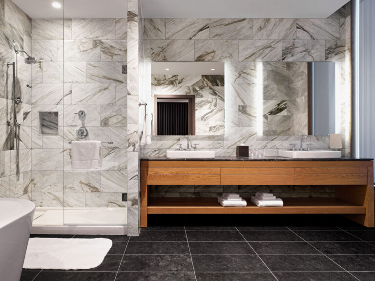 Hotel bathroom with two sinks, gray stone walls and a shower lined with gray stone.